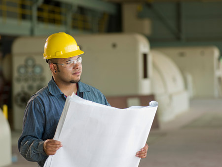 Engineer reading blueprints on site