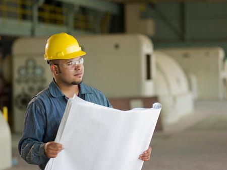 Ingenieur liest Baupläne vor Ort
