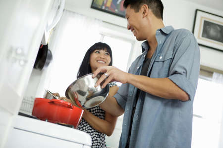 stovetop: Couple cooking together in kitchen LANG_EVOIMAGES