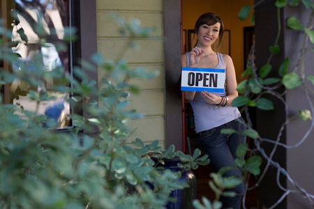 assured: Woman holding open sign in store
