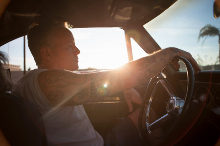lit image: Man driving vintage car at sunset