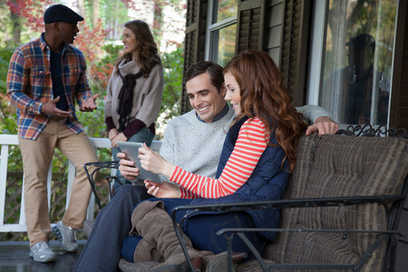 Couple using tablet computer on porch