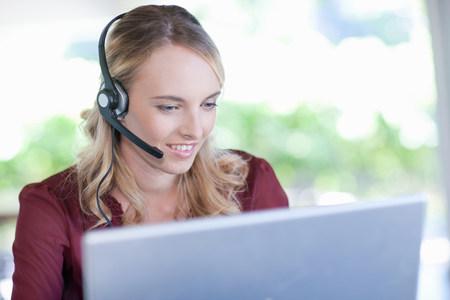 Businesswoman wearing headset at desk