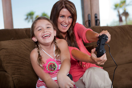 Mother and daughter playing video games LANG_EVOIMAGES