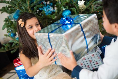 Children holding Christmas present LANG_EVOIMAGES