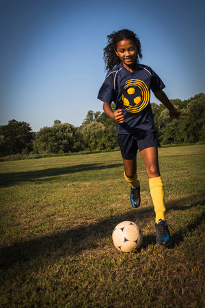 preadolescent: Girl playing soccer in field LANG_EVOIMAGES