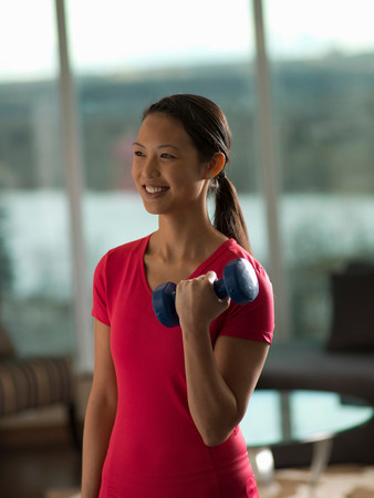 detoxing: Woman lifting weights in living room