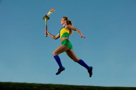 exerting: Brazilian runner carrying Olympic torch