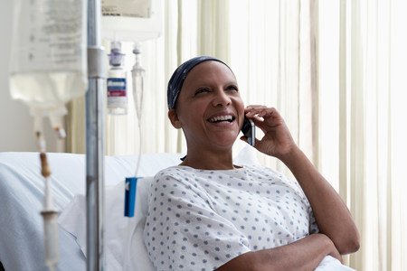 recuperating: Female hospital patient using cellphone LANG_EVOIMAGES