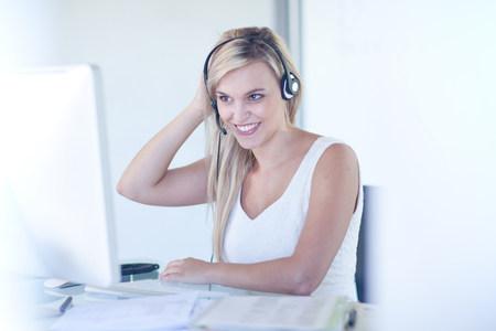 handsfree telephones: Businesswoman wearing headset at desk