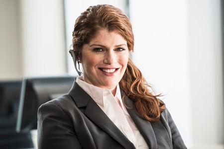 tiefe: Lächelnde Geschäftsfrau mit Headset LANG_EVOIMAGES