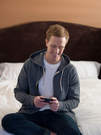 access point: Man using cell phone on bed