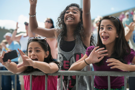 age 10 12 years: Three excited girls at a pop concert LANG_EVOIMAGES