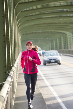 Woman running on urban bridge