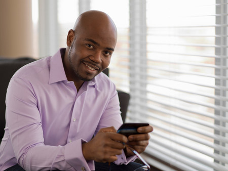 check ups: Businessman using cell phone on sofa
