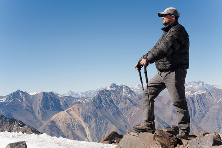 Hiker overlooking snowy mountains LANG_EVOIMAGES