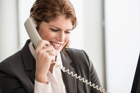 Smiling businesswoman talking on phone LANG_EVOIMAGES