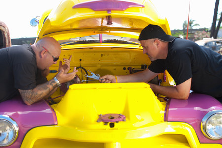 leaning on the truck: Mechanics working on colorful car