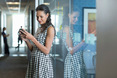 access point: Businesswoman using cell phone in office
