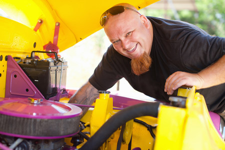 to mend: Mechanic working on colorful car