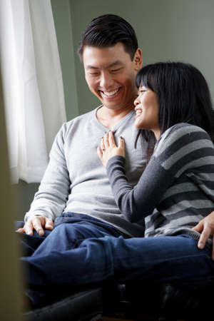 30 years old married couple: Couple relaxing together on sofa LANG_EVOIMAGES