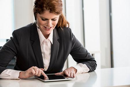 handsfree telephones: Businesswoman using tablet computer