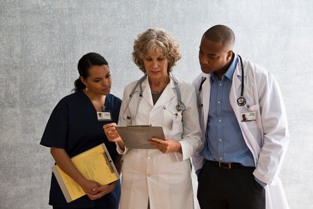 mixed age range: Portrait of nurse and doctors looking at clipboard LANG_EVOIMAGES
