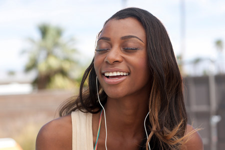 Woman listening to earphones outdoors LANG_EVOIMAGES