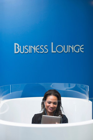 access point: Businesswoman relaxing in lounge LANG_EVOIMAGES