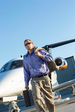 Businessman on airplane runway LANG_EVOIMAGES