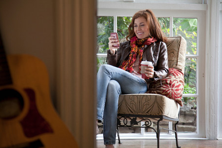 cross legged: Woman using cell phone in armchair LANG_EVOIMAGES
