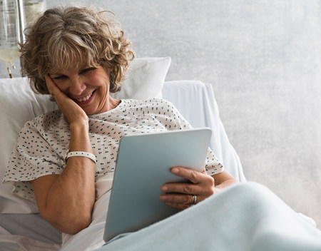 information superhighway: Female hospital patient with digital tablet,smiling