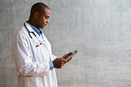 engrossed: Portrait of male doctor with digital tablet