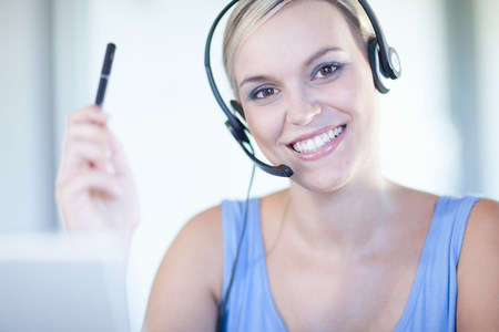 headshots: Businesswomen wearing headset at desk LANG_EVOIMAGES