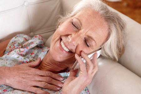 Oudere vrouw die op celtelefoon spreekt LANG_EVOIMAGES