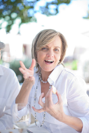 Older woman talking at table outdoors LANG_EVOIMAGES