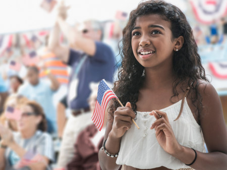 Girl holding american flag,crossing fingers LANG_EVOIMAGES