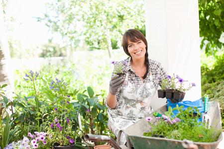 assured: Woman potting plants outdoors
