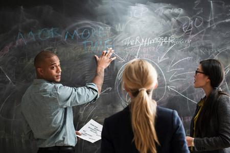 bi: Man writing on blackboard,colleagues watching