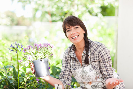 one mature woman only: Woman with potted plant in garden LANG_EVOIMAGES