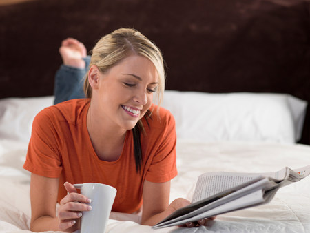Woman reading newspaper on bed