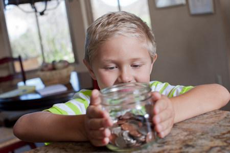Boy putting savings in glass jar LANG_EVOIMAGES