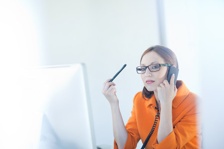 access point: Businesswoman talking on phone at desk