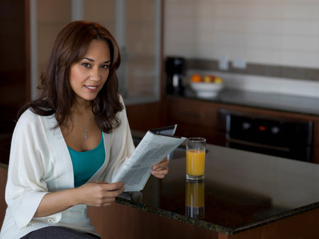25 29 years: Woman reading newspaper at breakfast LANG_EVOIMAGES