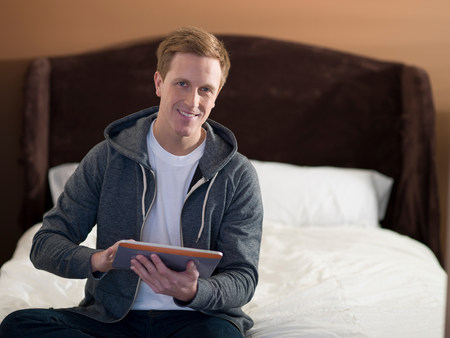 information superhighway: Man using tablet computer on bed