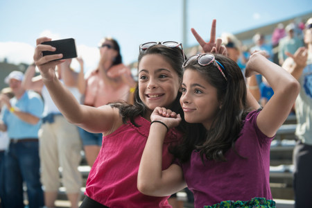Girls taking a picture of themselves at pop concert LANG_EVOIMAGES