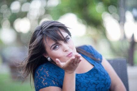 smooching: Woman blowing kiss outdoors