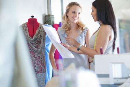 Dressmaker fitting client in studio