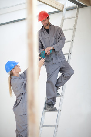 grays: Male and female laborer with electric drill on construction site LANG_EVOIMAGES