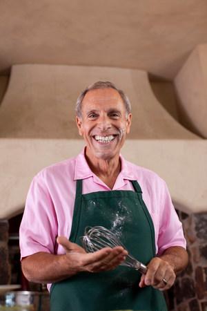 messy clothes: Older man baking in kitchen LANG_EVOIMAGES